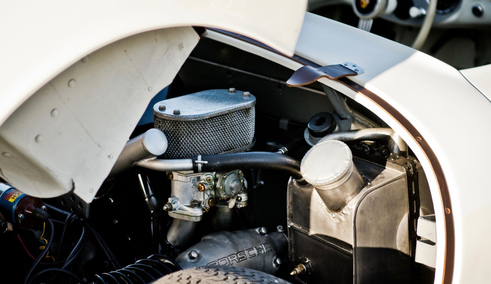 A view of the right cylinder bank, where one of the twin carburetors is enthroned. Below: one of two valve lids on each side—high-tech in the engine named after Ernst Fuhrmann.