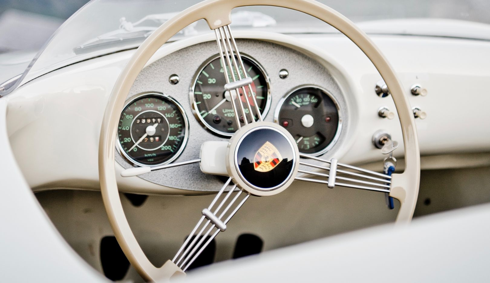 The narrow ivory-colored rim of the steering wheel and the triple spring spokes offer a clear view of the three instruments, with the rev counter at the center. Typical Porsche.